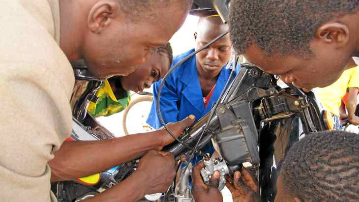 Teenagers learn to repair a motorcycle at a youth training centre in Korsimoro, a village in Burkina Faso. The centre is over-crowded, with long waiting lists and a severe shortage of equipment, and it is hoping to benefit from the new Canadian training project in Burkina Faso.