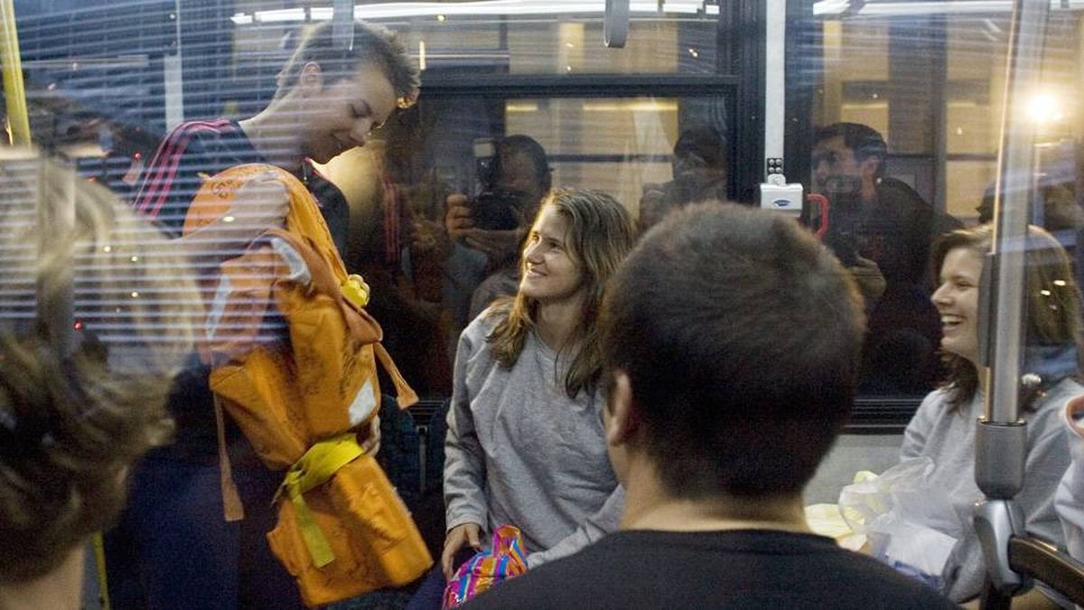 A student shows off a life preserver from the sunken ship S.V. Concordia as survivors board a shuttle bus after arriving at Toronto's Pearson International Airport on Monday February 22, 2010.