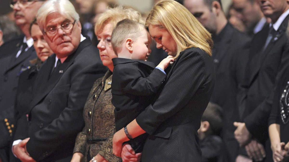 Christine Russell, wife of Sgt. Ryan Russell, has an intimate moment with her son, Nolan, during her husband's funeral. His parents are at left.