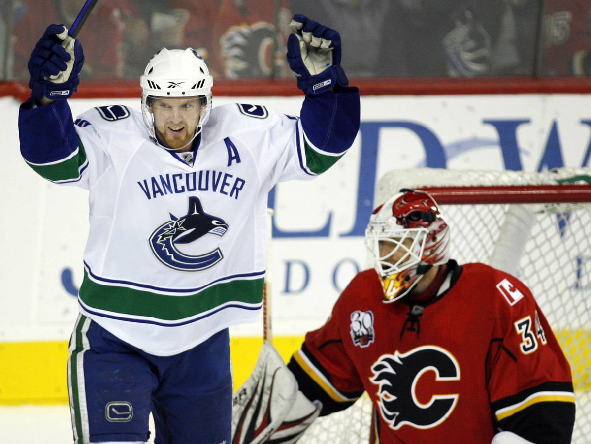 Vancouver Canucks' Henrik Sedin, left, from Sweden, celebrates teammate Mikael Samuelsson's goal as Calgary Flames goalie Miikka Kiprusoff, from Finland, sweeps the puck out of the net during third period NHL hockey action in Calgary, Friday, Oct. 16, 2009. The Calgary Flames beat the Vancouver Canucks 5-3.THE CANADIAN PRESS/Jeff McIntosh