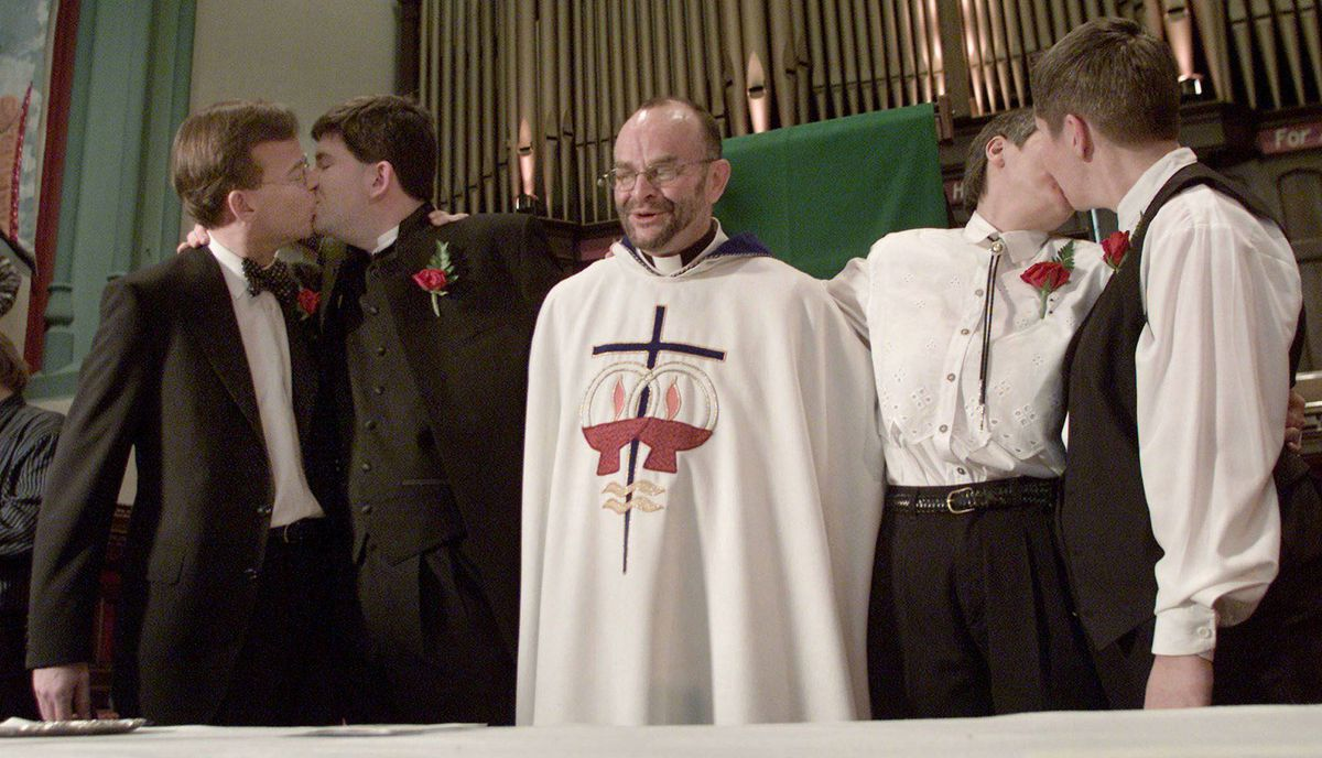 Believed to be the first marriage licences issued to gay couples in 2001. Kevin Bourassa (L) and Joe Varnell along with Anne Vautour (second right) and Elaine Vautour kiss as Reverend Brent Hawkes looks on following a wedding ceremony in a Toronto church January 14, 2001.