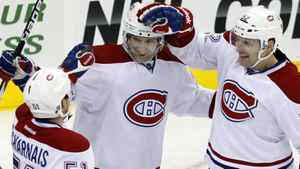 Montreal Canadiens' David Desharnais, , left, and Mathieu Darche, right, celebrate a goal by Erik Cole, center, during the third period of an NHL hockey game against the New Jersey Devils in Newark, N.J., Saturday, Dec. 10, 2011. Canadiens won 2-1. (AP Photo/Mel Evans)