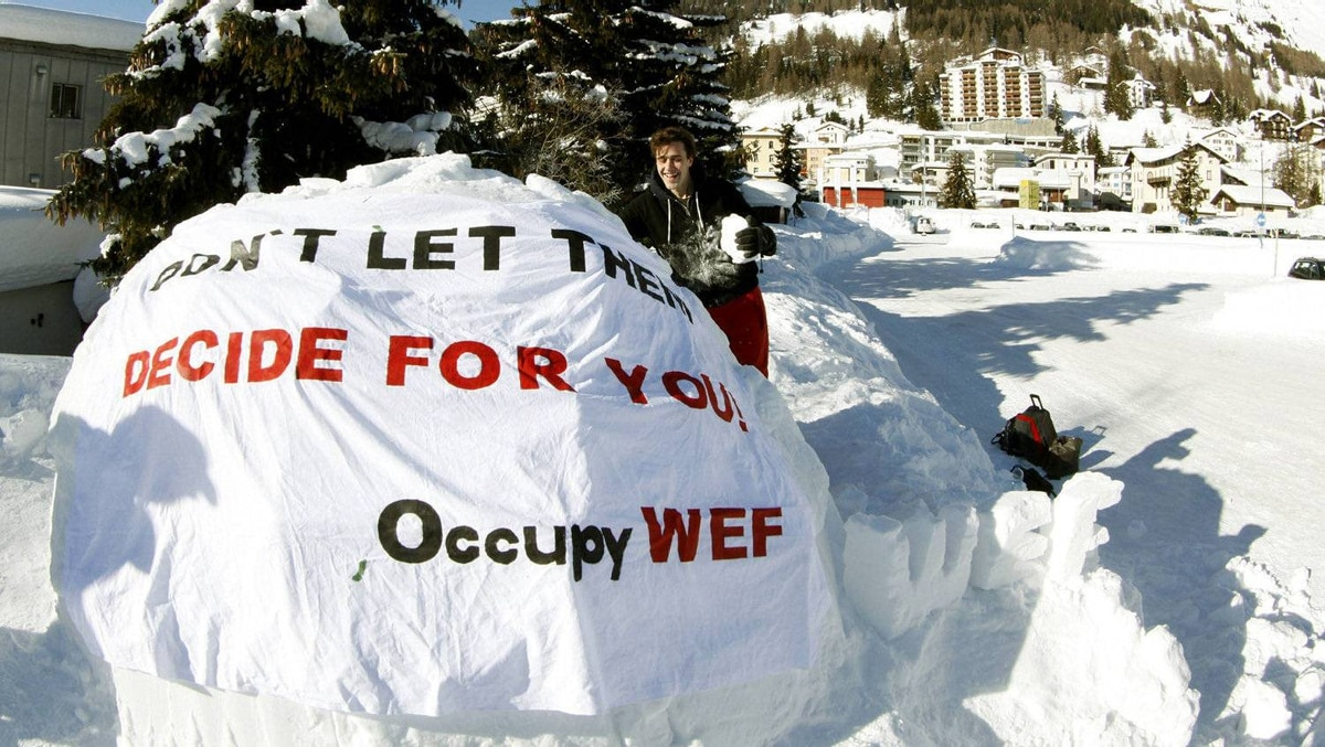 Protester David Roth attaches a banner to the first igloo at the Occupy WEF site.