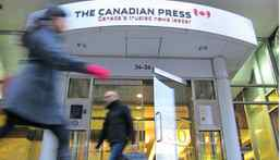 Pedestrians walk past The Canadian Press head office entrance in Toronto