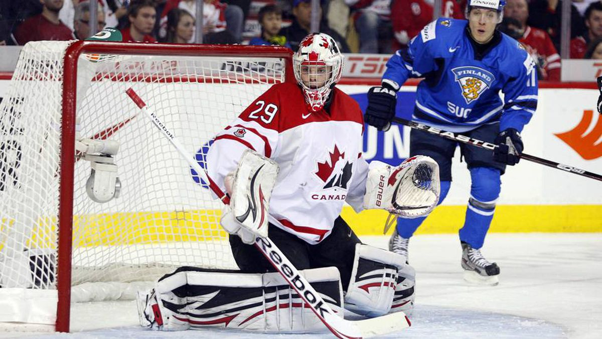 Team Canada goalie Mark Visentin, left, follows the play as Finland's Markus Granlund looks on during the first period.