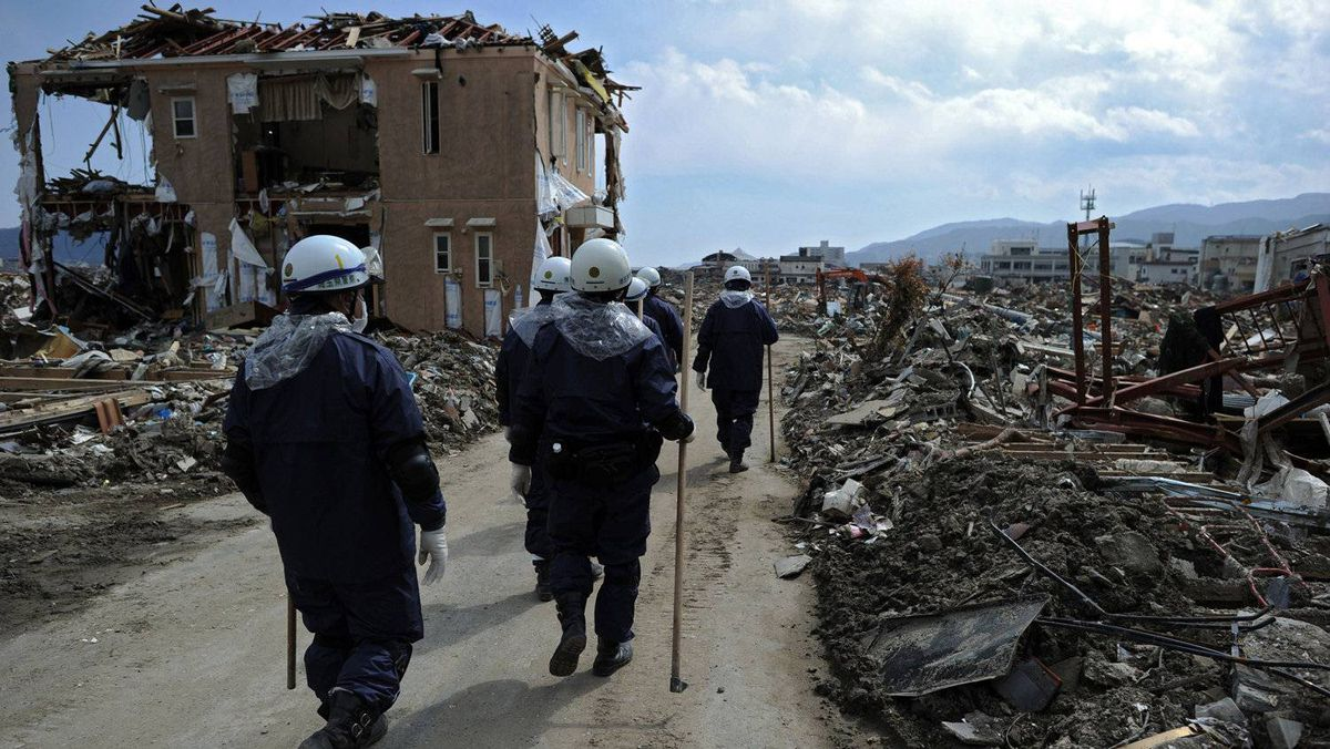 Rescue workers walk among destroyed houses and debris in the tsunami-damaged city of Rikuzen-Takata on March 24, 2011.