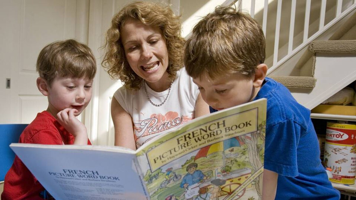 Sindy Preger reads French books to her 4-year-old twin boys Levi and Reuben.