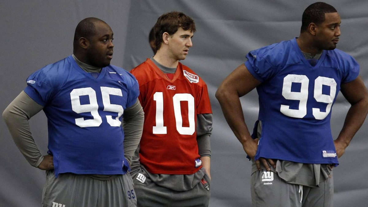 New York Giants teammates Rocky Bernard (95), Eli Manning (10), and Chris Canty (99) watch practice for the NFL Super Bowl XLVI in Indianapolis, February 4, 2012. The Giants will play the New England Patriots on February 5. REUTERS/Jeff Haynes