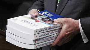 Finance Minister Jim Flaherty holds copies of his budget in the House of Commons on March 22, 2011.