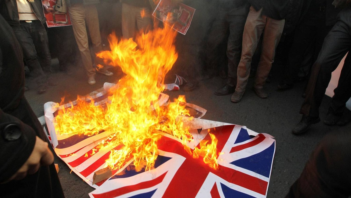 Iranian protesters burn the British flag outside the embassy in Tehran on November 29, 2011.