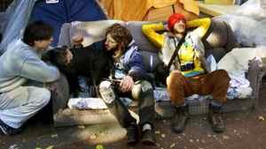 Squatters gather outside their tents that surround the now vacant Woodward's Department Store building on the downtown eastside of Vancouver Wednesday, Oct. 30, 2002.