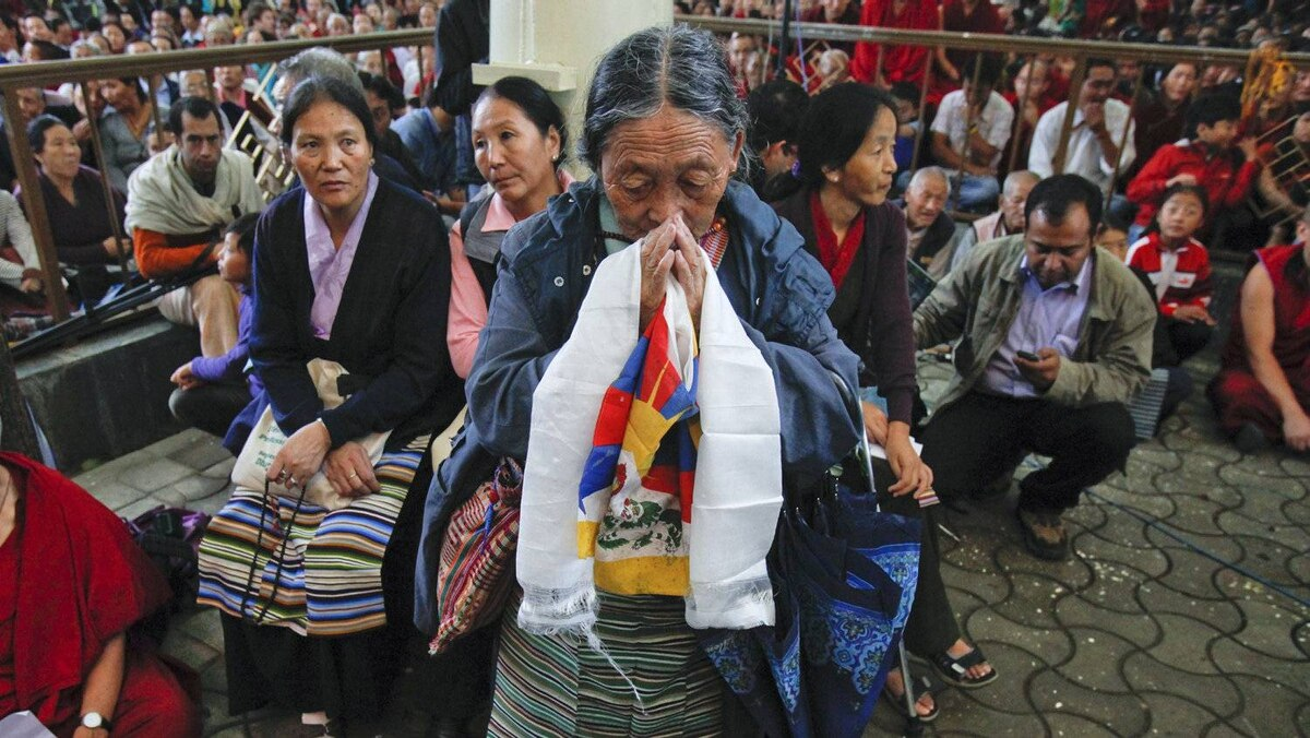 A woman prays with a Tibetan flag outside the ceremony. Beijing has never publicly budged from their position on Tibet, stating Tibetans have no legitimacy or rights to negotiate.