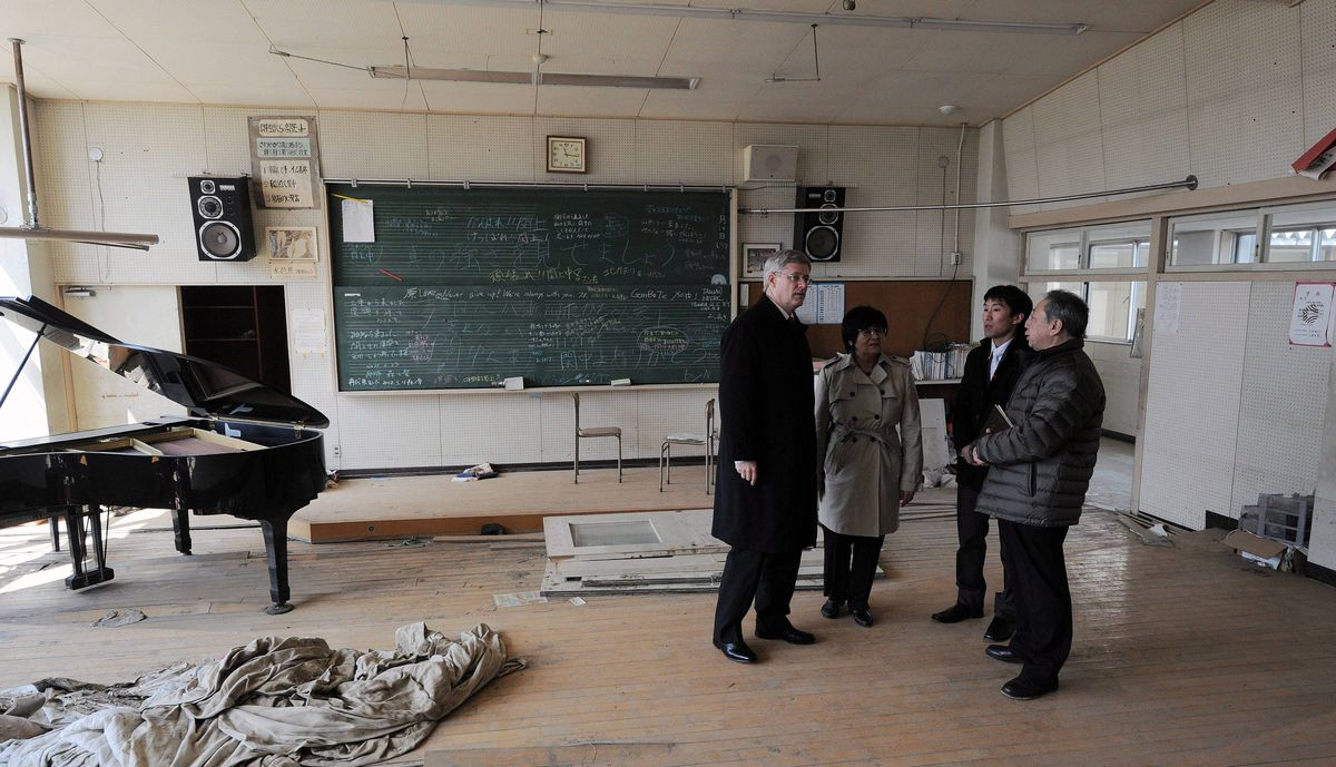 Prime Minister Stephen Harper, left, and Minister of International Cooperation Bev Oda, second from left, talk with Principal Sumio Takahashi and a translater as they tour Yuriage Junior High School near Sendai, Japan, on Monday, March 26, 2012.