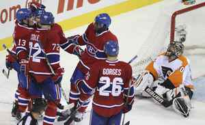 Philadelphia Flyers goalie Ilya Bryzgalov (R) watches as Montreal Canadiens Mike Cammalleri (13) celebrates his goal with teammates during third period NHL hockey action in Montreal October 26, 2011.