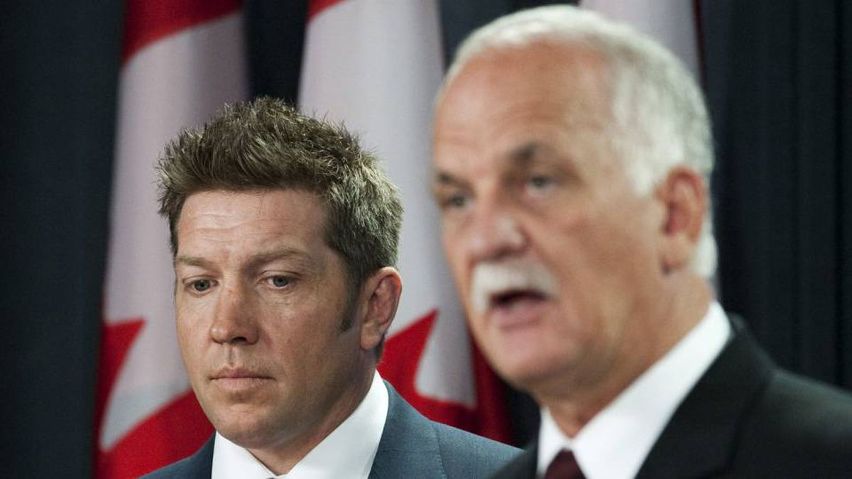 Former NHL player Sheldon Kennedy listens to Public Safety Minister Vic Toews as he unveils legislation that toughens requirements for criminal pardons at an Ottawa news conference on May 11, 2010.
