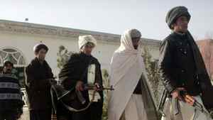 Former Taliban militants walk to hand over their weapons during a joining ceremony with the Afghan government in Herat, Afghanistan Wednesday, Dec. 28, 2011.