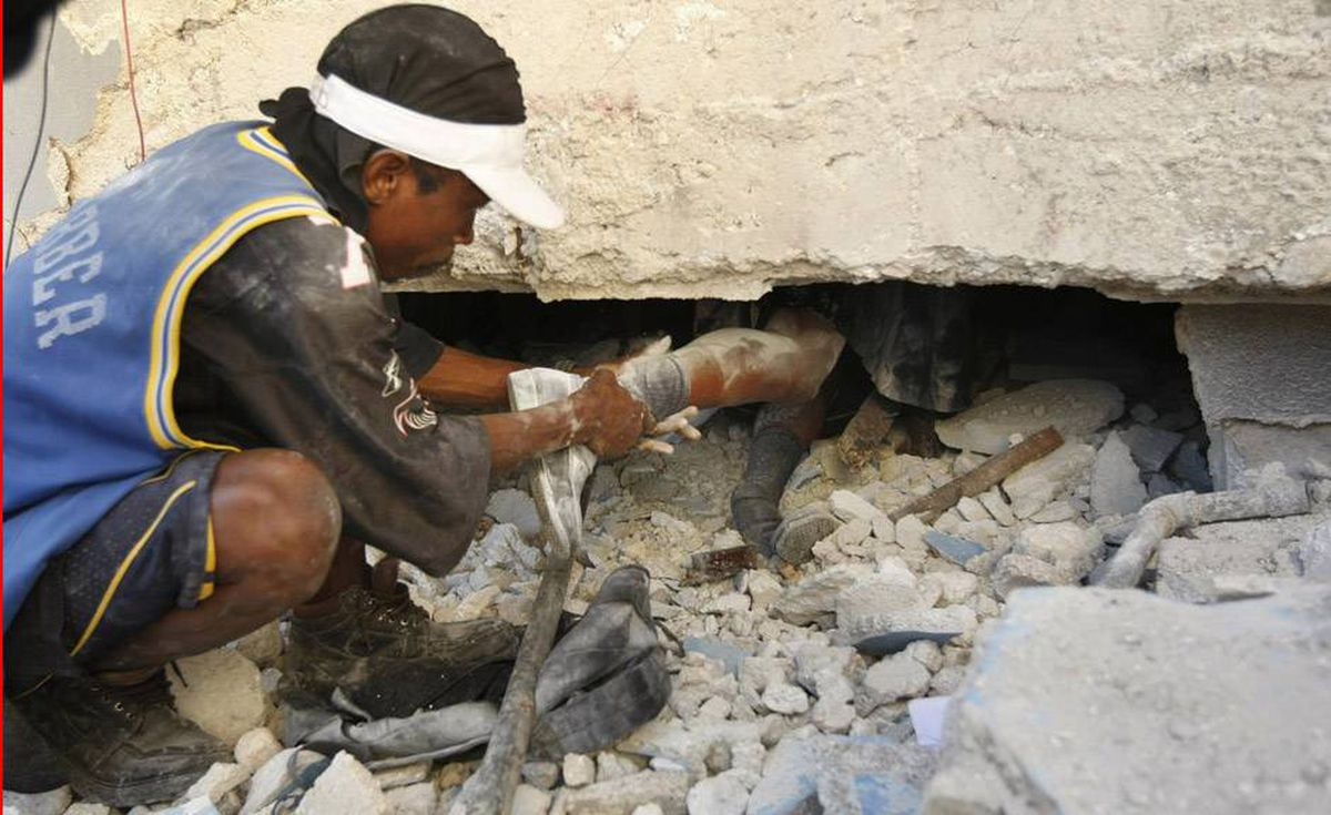 A man pulls on the leg of a school girl who died in the rubble of St. Gerard Church and School in Port-au-Prince, Thursday, Jan. 14, 2010. Several students and teachers died when the building collapsed.