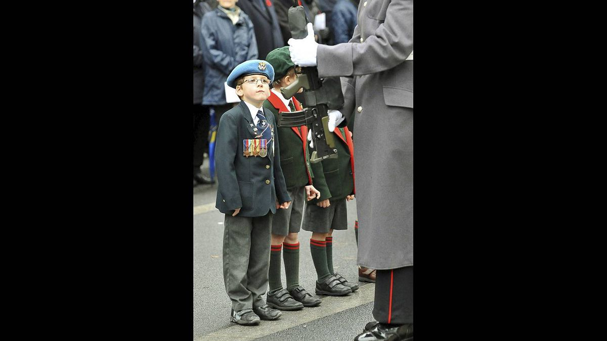 Seven-year-old Jonny Osborne, wearing the medals of his great-great uncle, Sapper Lawrence Burton, attends a service of remembrance at the Cenotaph in London, Nov. 11, 2010, to mark the anniversary of Armistice Day, when peace returned to Europe at the end of the First World War.