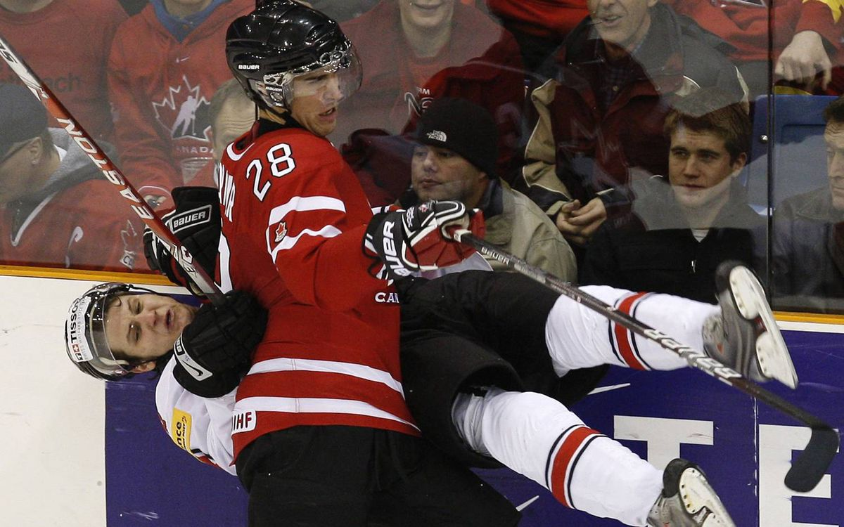 Canada's Patrice Cormier hits Switzerland's Jannik Fischer during the third period of their semi-final game at the 2010 IIHF U20 World Junior Hockey Championship in Saskatoon,