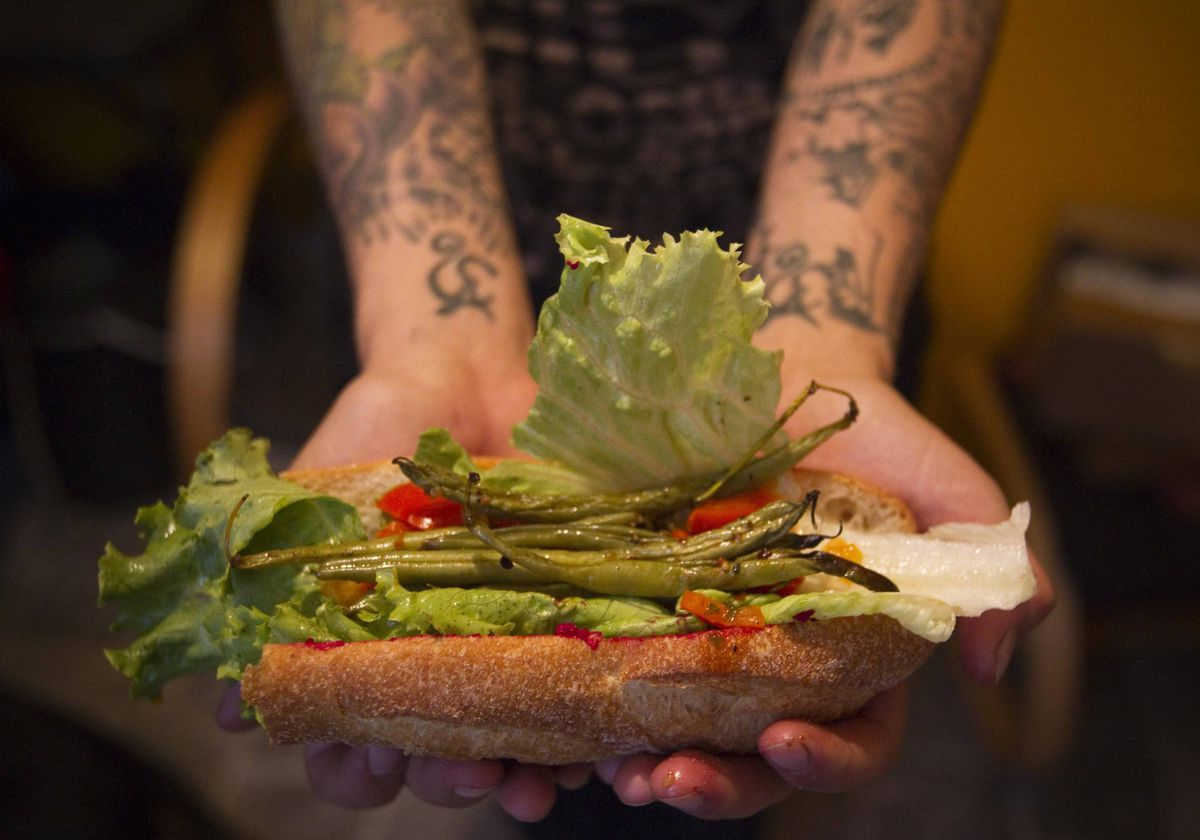 May Wollf a practising 'freegan', holds a sandwich that is made entirely out of found or donated food in Vancouver, British Columbia.