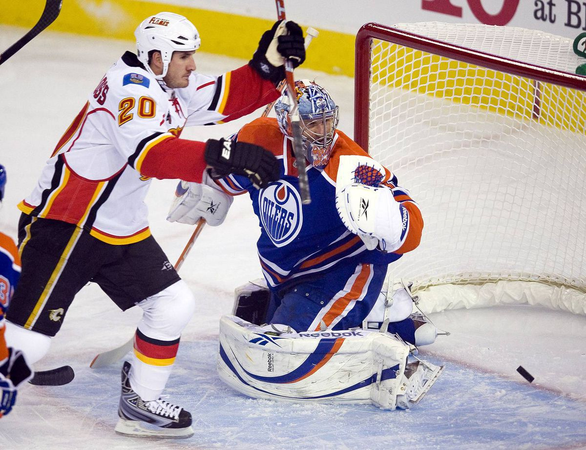 Calgary Flames' Curtis Glencross celebrates his goal against Edmonton Oilers goaltender Nikolai Khabibulin during first-period NHL hockey action in Edmonton on Saturday, October 3, 2009.