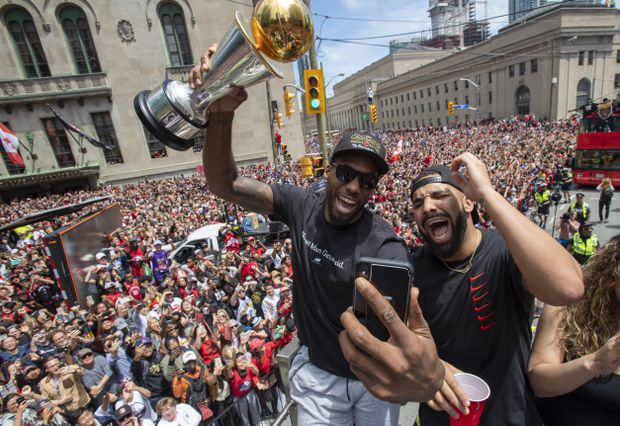 ce8b5795250 Kawhi Leonard holds his MVP trophy while celebrating with Drake during the  Championship parade.