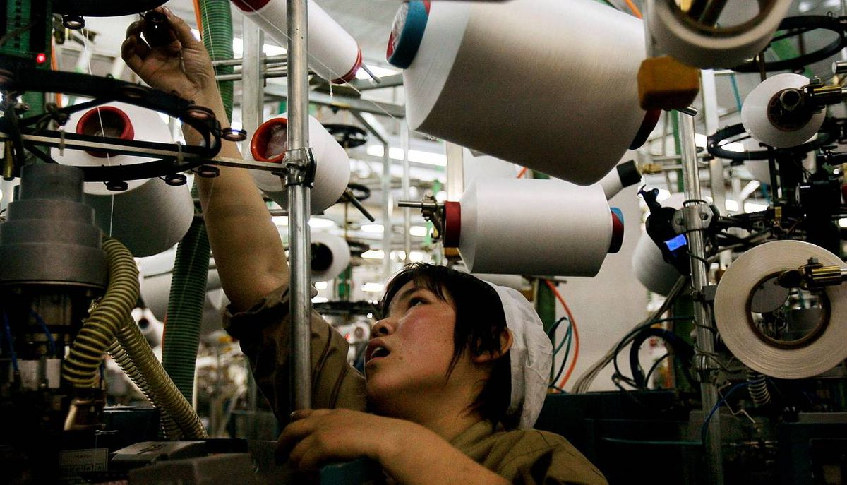 A worker operates a machine to make socks at a Langsha Socks Group production plant in Yiwu, China.