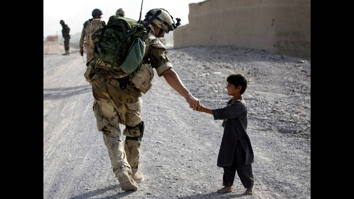 A Canadian soldier shakes hands with an Afghan boy during a joint patrol with Afghan National Army troops near Panjwaii village, Kandahar province, southern Afghanistan, July 13, 2007.