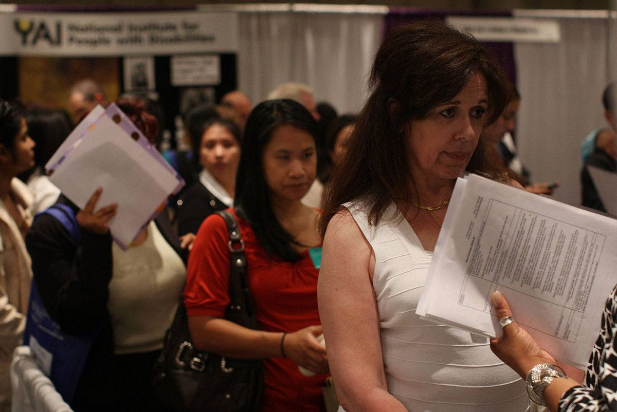 Job seekers wait in line to speak with job recruiters at a job fair for businesses in the medical field in New York.