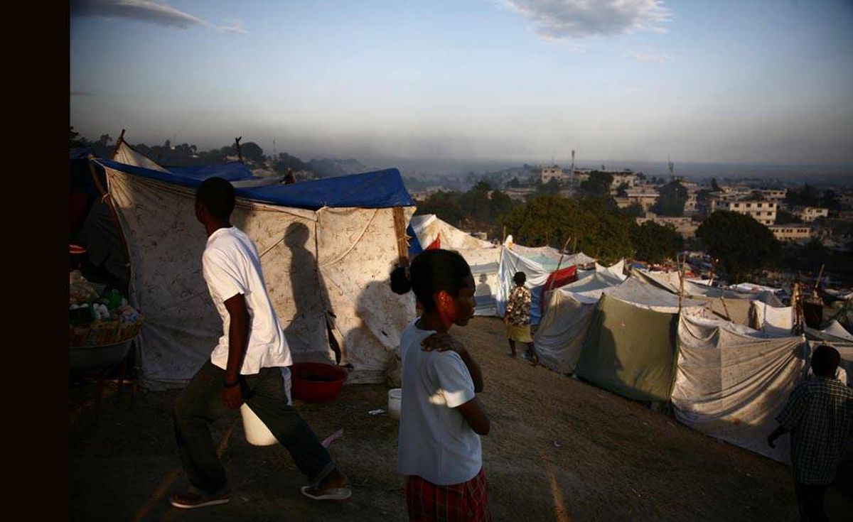 People walk at sunrise in the displaced persons' camp at the only golf course in Port-au-Prince.