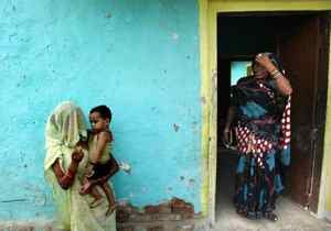 An Indian woman plays with her child outside her house ahead of Mother's Day, in Allahabad, India, Sunday, May 6, 2012. Mother's Day will be celebrated on May 13.