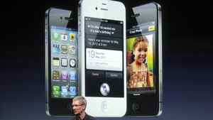 Apple CEO Tim Cook speaks in front of an image of the iPhone 4S.