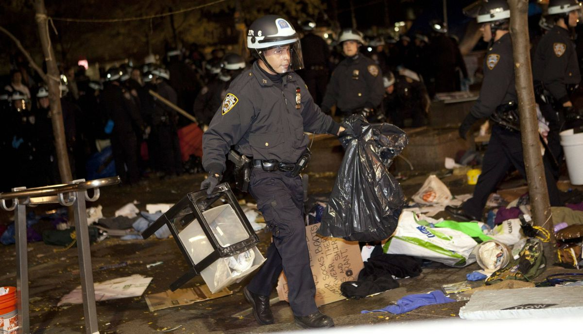 A police officer carries trash through Zuccotti Park, the longtime encampment for Occupy Wall Street protesters in New York, as the cleanup effort begins early Tuesday, Nov. 15, 2011.