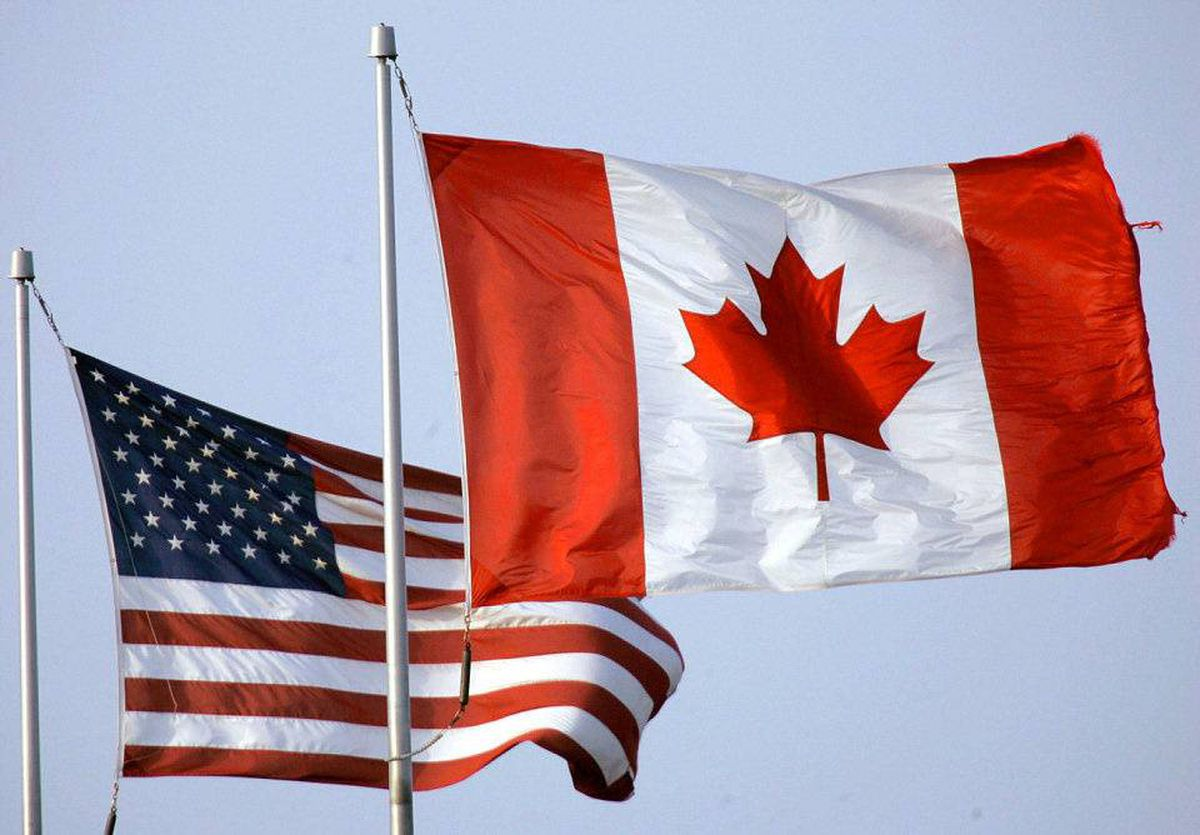 The United States flag and the Canadian flag fly side by side at the Walden Galleria Mall in Cheektowaga, N.Y.