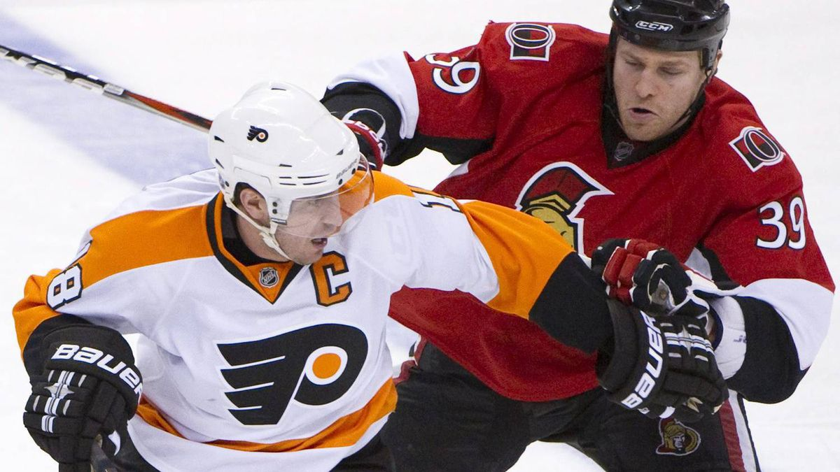 Philadelphia Flyers' Mike Richards skates with the puck as he holds off Ottawa Senators' Matt Carkner during third period NHL hockey action at the Scotiabank Place in Ottawa on Saturday, February 26, 2011. The Senators upset the Flyers 4-1. THE CANADIAN PRESS/Sean Kilpatrick