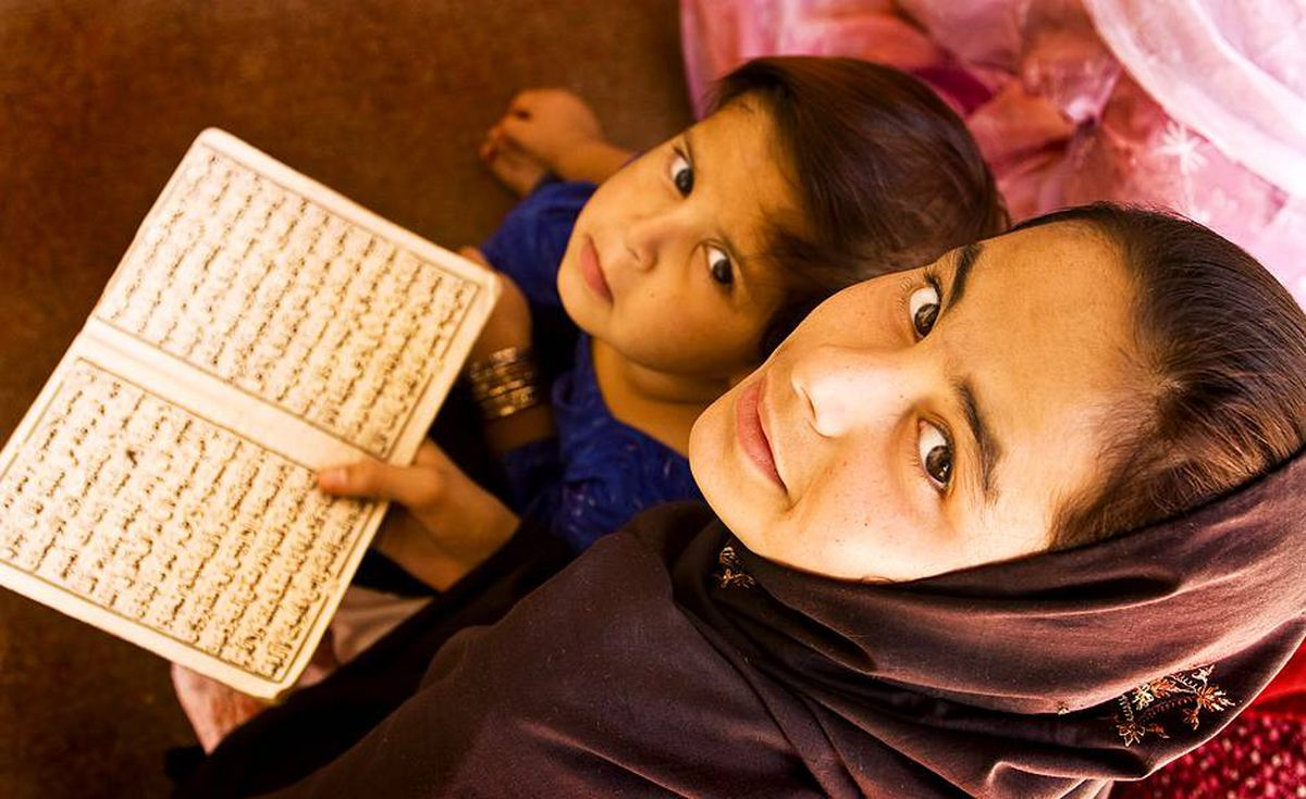 Two girls work on reading their prayers and learning to chant the Koran at home. With an overall literacy rate in Afghanistan of only 28 per cent and an even lower rate among women, simply learning to read is a significant accomplishment for these girls.
