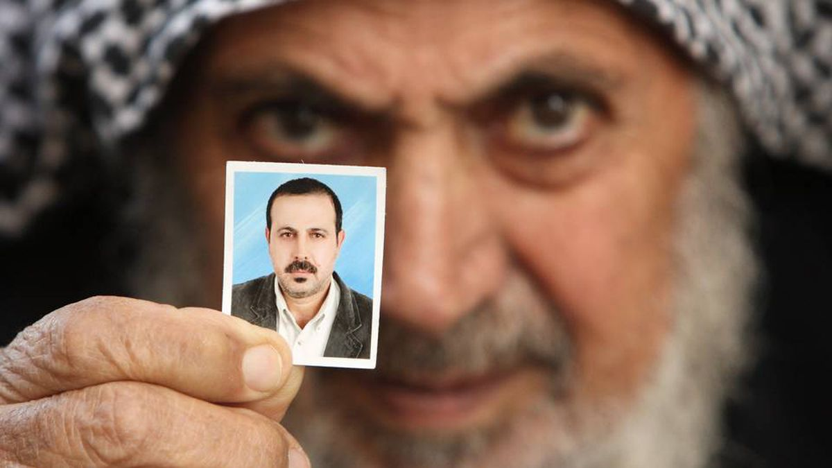 Father of senior Hamas military commander Mahmoud al-Mabhouh poses with his son's picture at his family house in the northern Gaza Strip January 29, 2010.