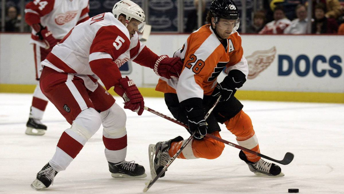 Detroit Red Wings defenseman Nicklas Lidstrom and Philadelphia Flyers right wing Claude Giroux compete for the puck during the second period of their NHL hockey game in Detroit, Michigan February 12, 2012. The Red Wings won 4-3. REUTERS/Rebecca Cook