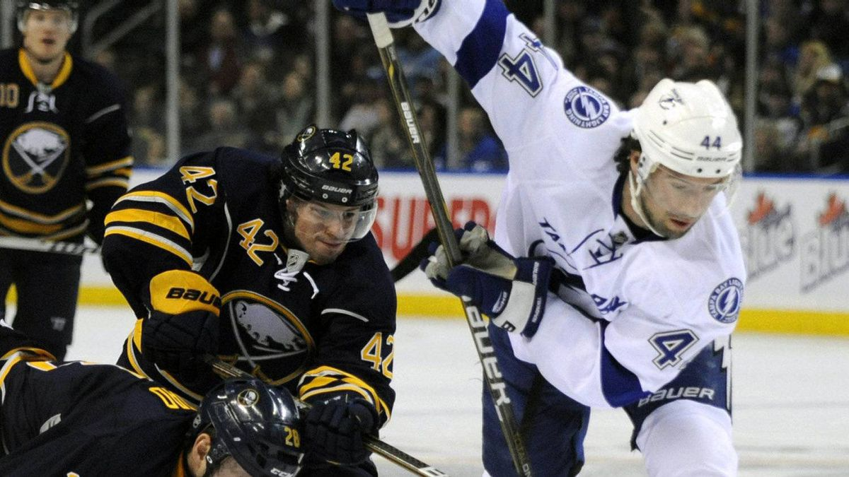 Buffalo Sabres' Paul Gaustad (28) and Nathan Gerbe (42) battle for the puck with Tampa Bay Lightning' Nate Thompson (44) during the first period of an NHL hockey game in Buffalo, N.Y., Saturday, Feb. 11, 2012. The Lightning won 2-1. (AP Photo/Gary Wiepert)