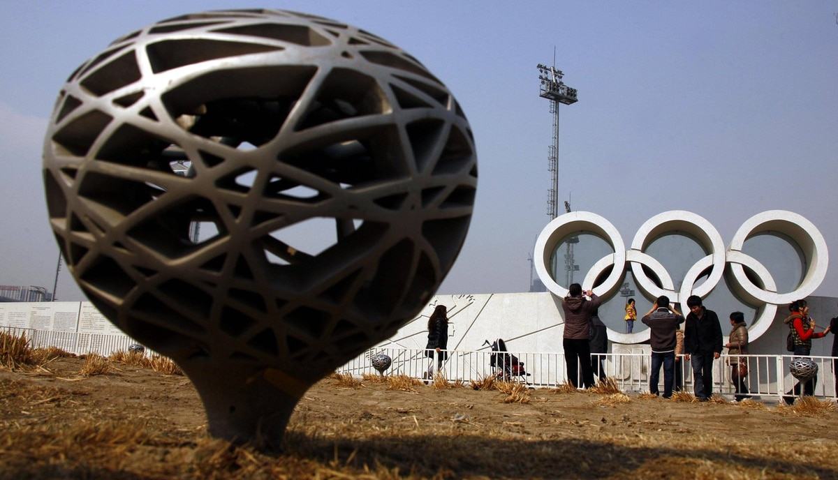 "Tourists pose for photographs on cement Olympic rings next to a lamp resembling the National Stadium, also known as the ""Bird's Nest"", in the former Olympic Green area in Beijing March 23, 2012."