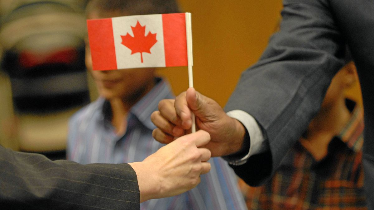 New Canadian citizens receive Canadian flags after a citizenship ceremony at the Toronto's CIC office at St. Clair Ave.