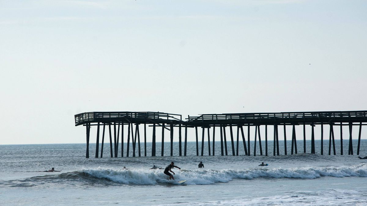 A man surfs near the Virginia Beach Fishing Pier, which suffered damage from Hurricane Irene, on August 28, 2011 in Virginia Beach, Virginia.