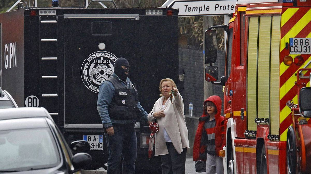 A woman speaks with a police officer near the apartment building under siege in Toulouse, on March 22, 2012.