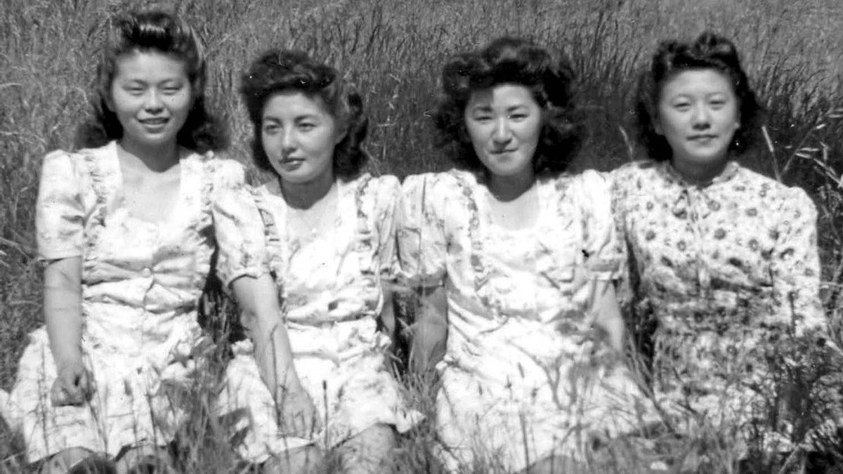 Four young women, originally sent to internment camps in the Slocan Valley during the Second World War, take a break while working on a local family farm in 1946.