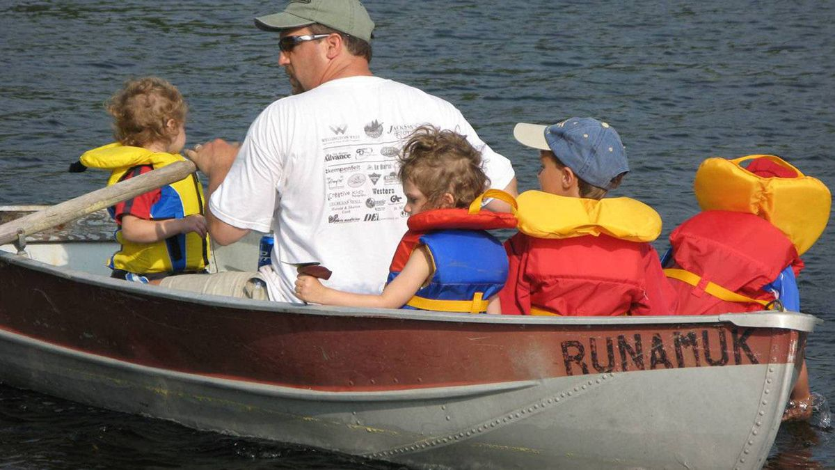 """Krista LaRiviere's husband, Andrew Zyp, with their children, Marco and Chloe, and cousins Matthew and Ryan, in the rowboat they call the """"Runamuk."""" It has a hole in it, takes in a lot of water, but nobody seems to mind, Ms. LaRiviere says."""