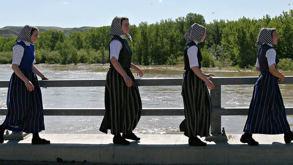 Young Hutterite women from the Standard Colony walk across a bridge over the Red Deer River near Drumheller, Alta., Monday, June 20, 2005.