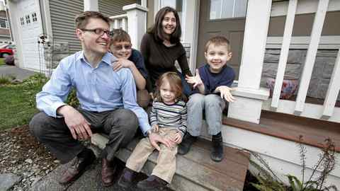 Steve and Tanya Wellburn and their children Fiona, 2, Gregory, 6, and Crispin,11, pose for a photo on the front deck of their home where Stephen Harper made an announcement during his election campaign tour in Saanich, where conservative candidate Troy DeSouza is running in the Esquimalt-Juan de Fuca riding, near Victoria, BC, Monday morning.
