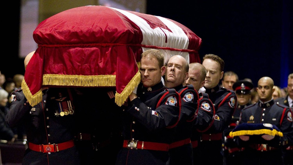 Pallbearers carry the casket of Sgt. Ryan Russell during his funeral in Toronto on Tuesday, January 18, 2011. Thousands honoured Sgt. Russell who was killed by a stolen snowplow on January 12 in Toronto.