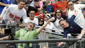 A television cameraman catches a foul ball hit by Minnesota Twins' Justin Morneau during the ninth inning of the Twins' American League MLB baseball game against the Texas Rangers at Target Field in Minneapolis, April 14, 2012. Texas won 6-2. REUTERS/Eric Miller