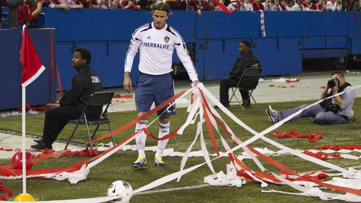 David Beckham clears the streamers tossed from the stands before his corner kick.